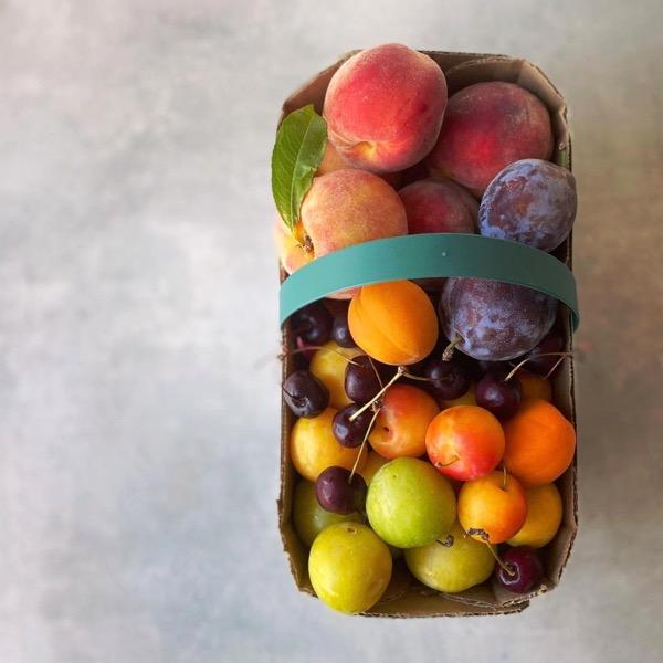 A basket of farm-fresh stone fruit from Bushel & Peck.