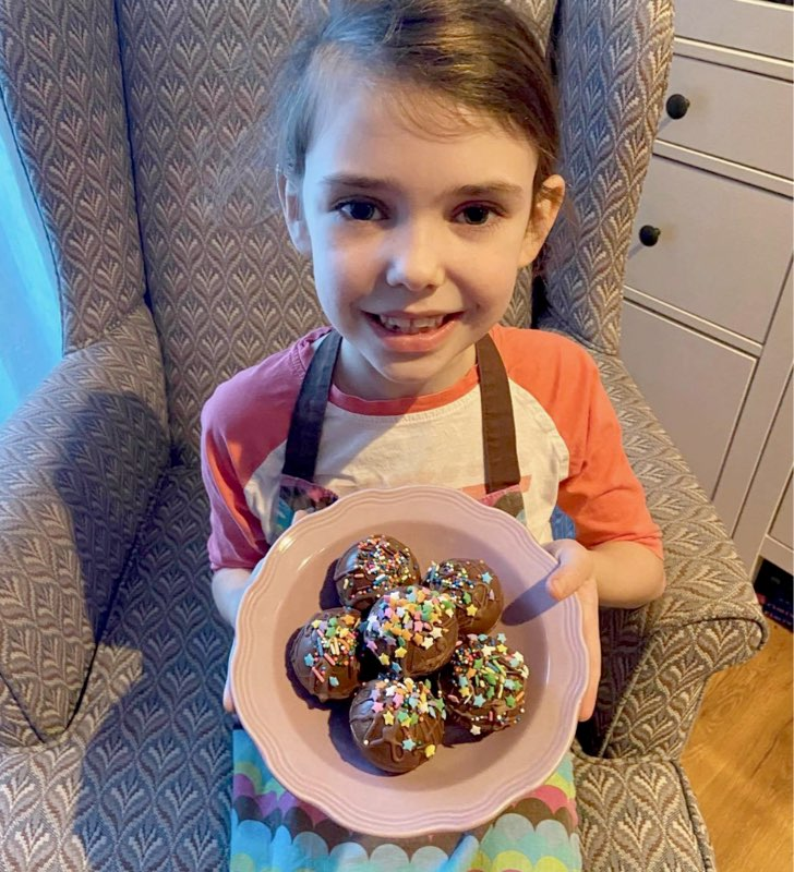 A little girl in an apron smiles and presents a bowl of chocolate and rainbow sprinkle baked treats.