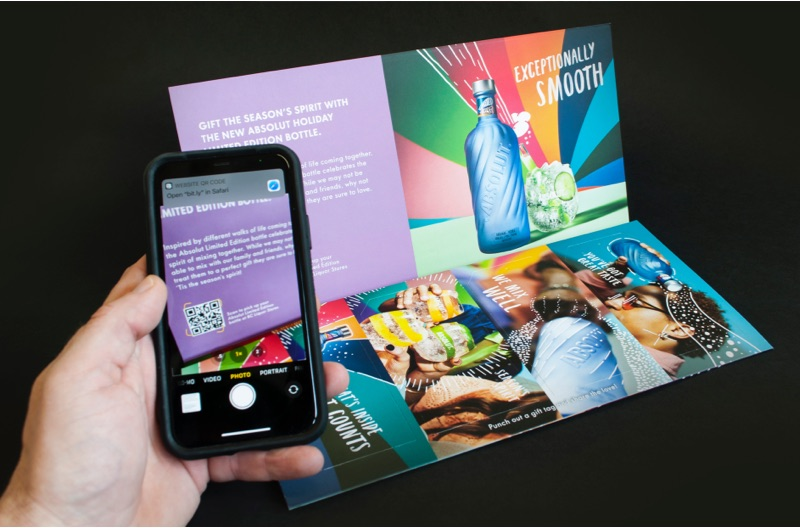 A person takes a cell phone photo of a QR code that appears on an Absolut Vodka direct mail piece.