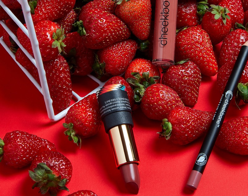 Cheekbone Beauty lipstick, stain and lip liner surrounded by strawberries.