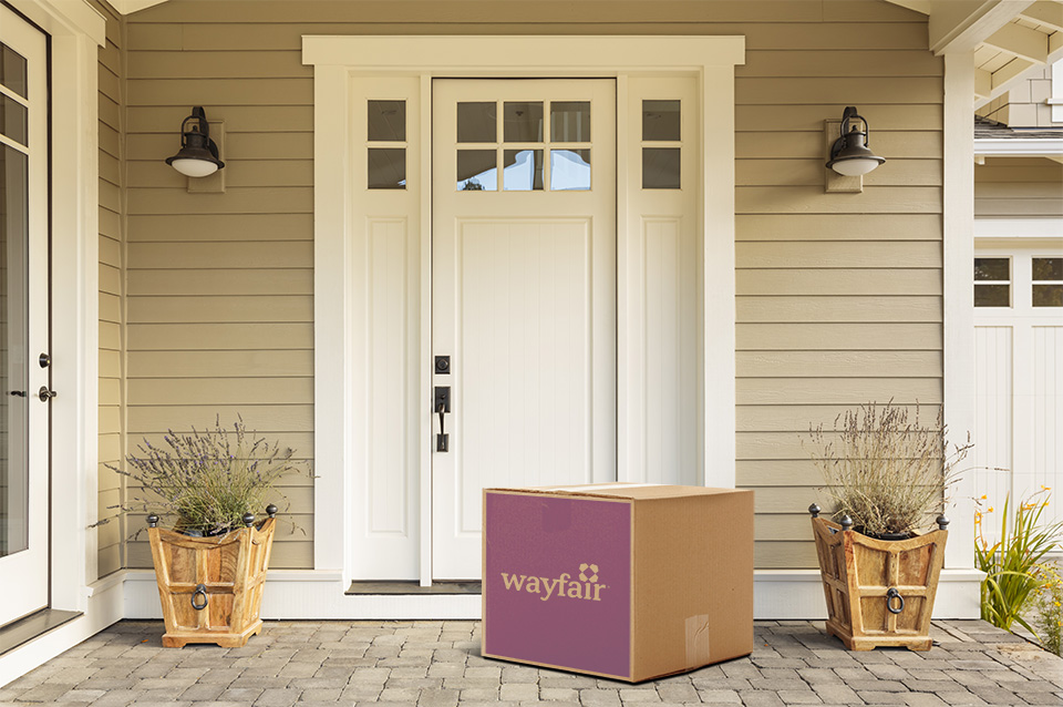Boîte de wayfair.ca déposée devant la porte d'entrée blanche d'une maison