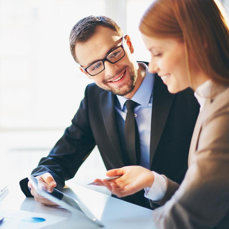 Deux employés comparant des notes et s'échangeant des idées en souriant.