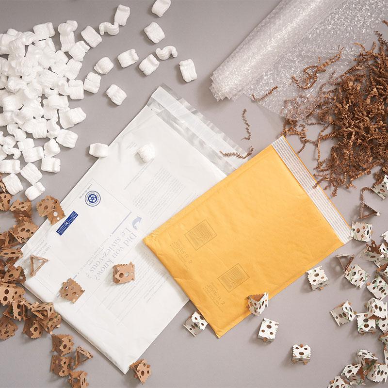 Enveloppes en polyéthylène et enveloppes protectrices matelassées de Postes Canada, entourées de matériel d'emballage.