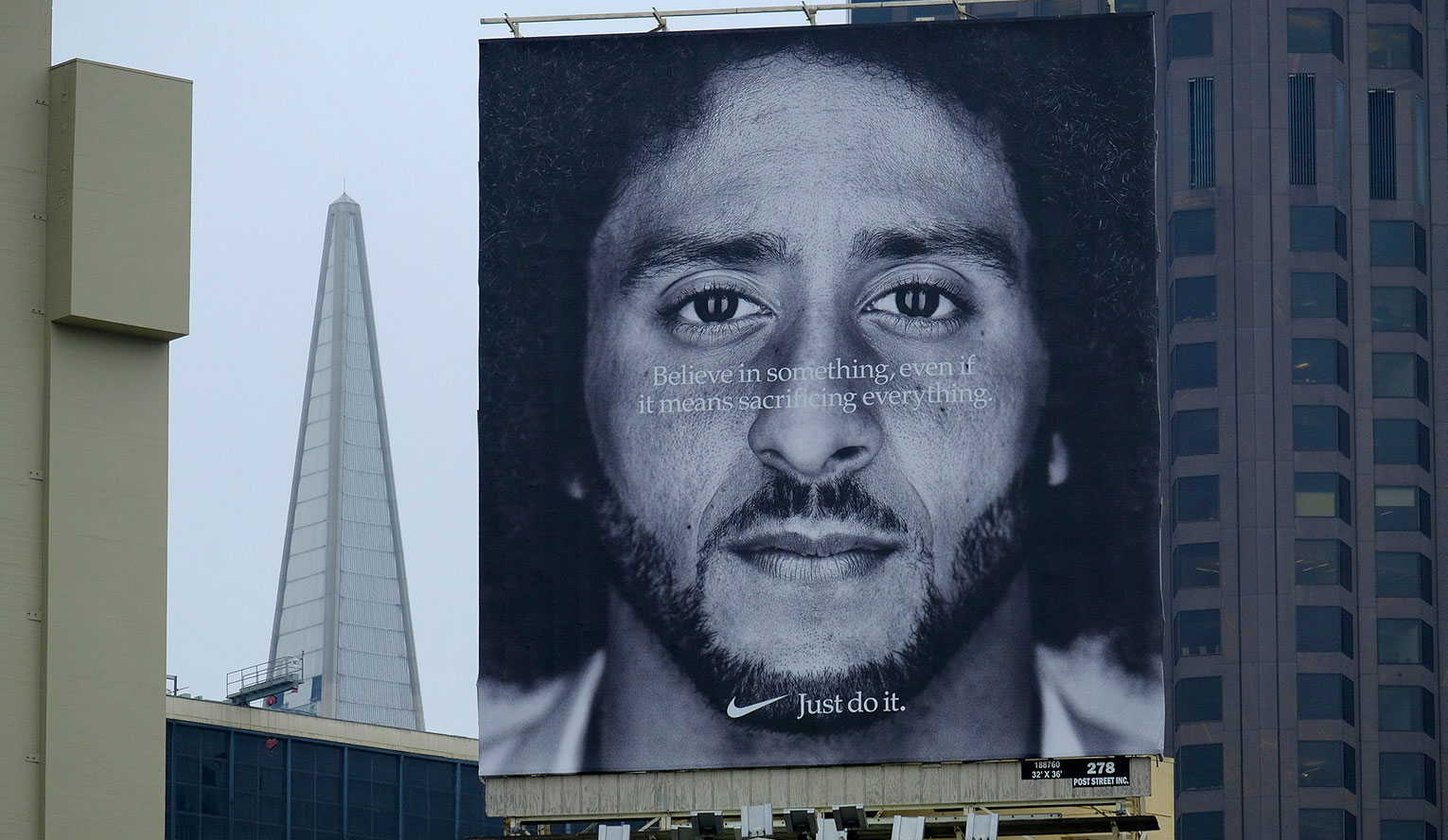 "A giant billboard Nike ad featuring the face of kneeling quarterback Colin Kaepernick with the text, ""Believe in something, even if it means sacrificing everything. Just do it."" Source: The New York Times."
