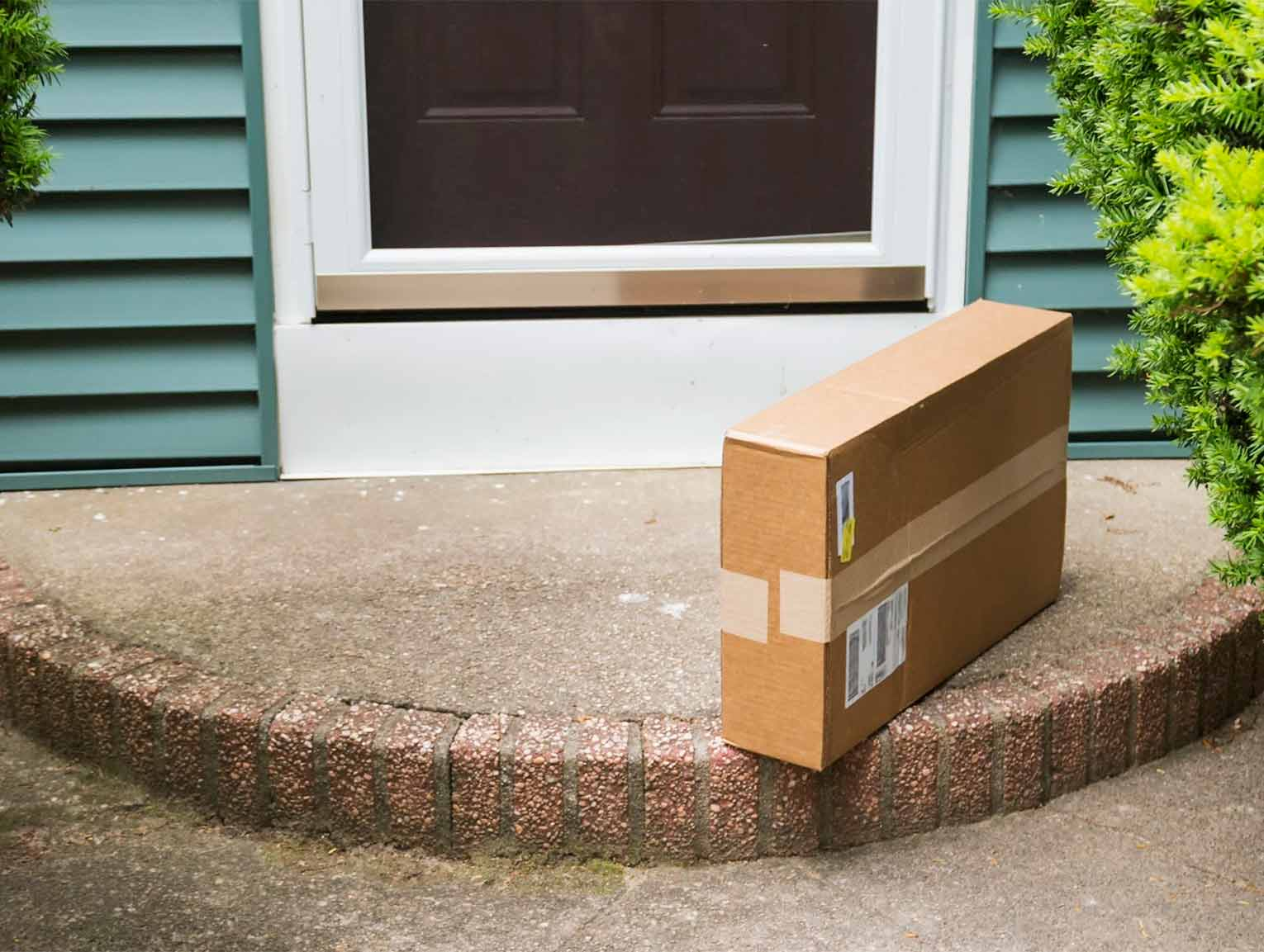 A brown box sits on a front stoop.