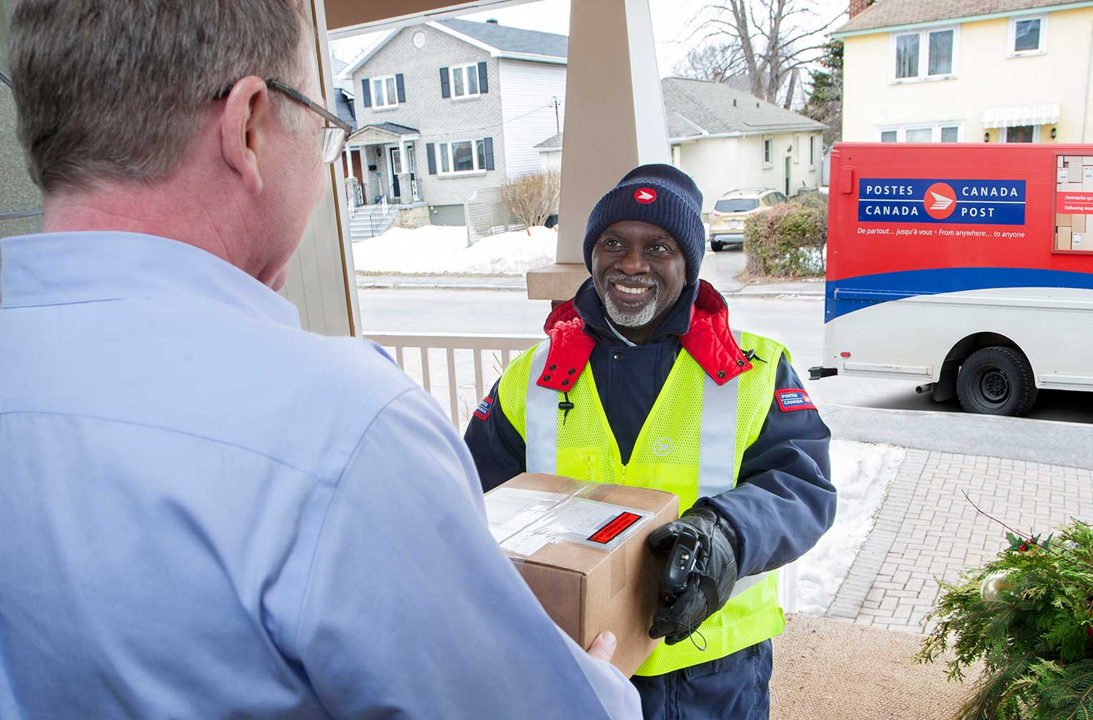 A Canada Post courier delivers a package to a man at his home.