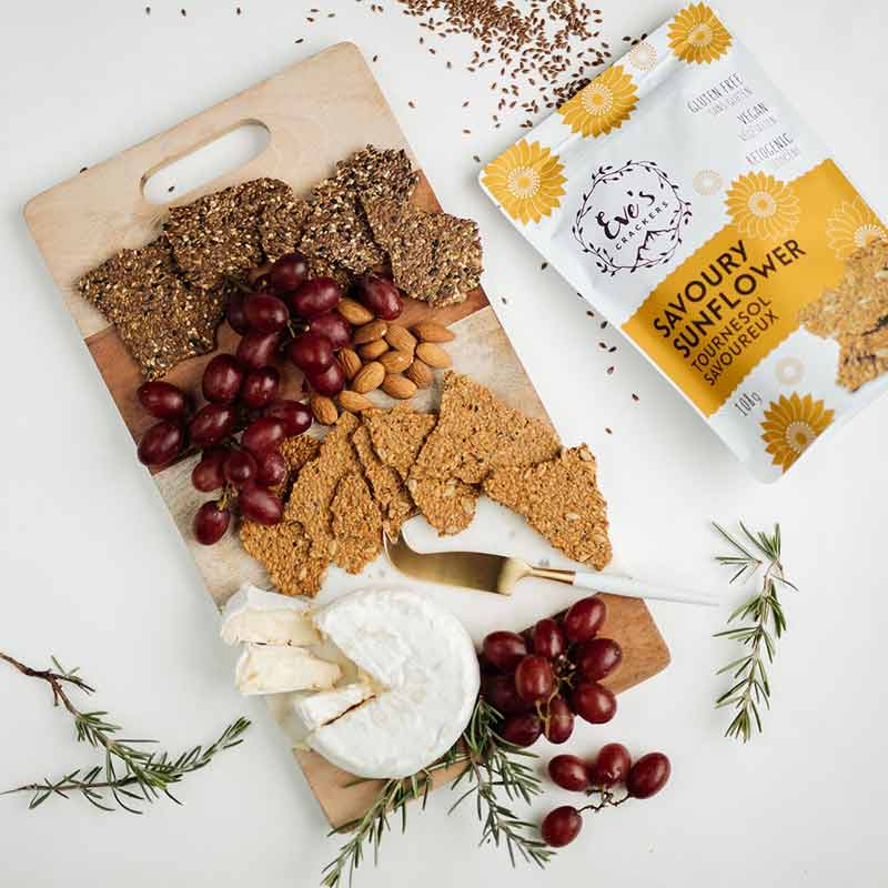 A cheese platter from Eve's Crackers filled with Savoury Sunflower crackers, red grapes, almonds and a round of Brie cheese.