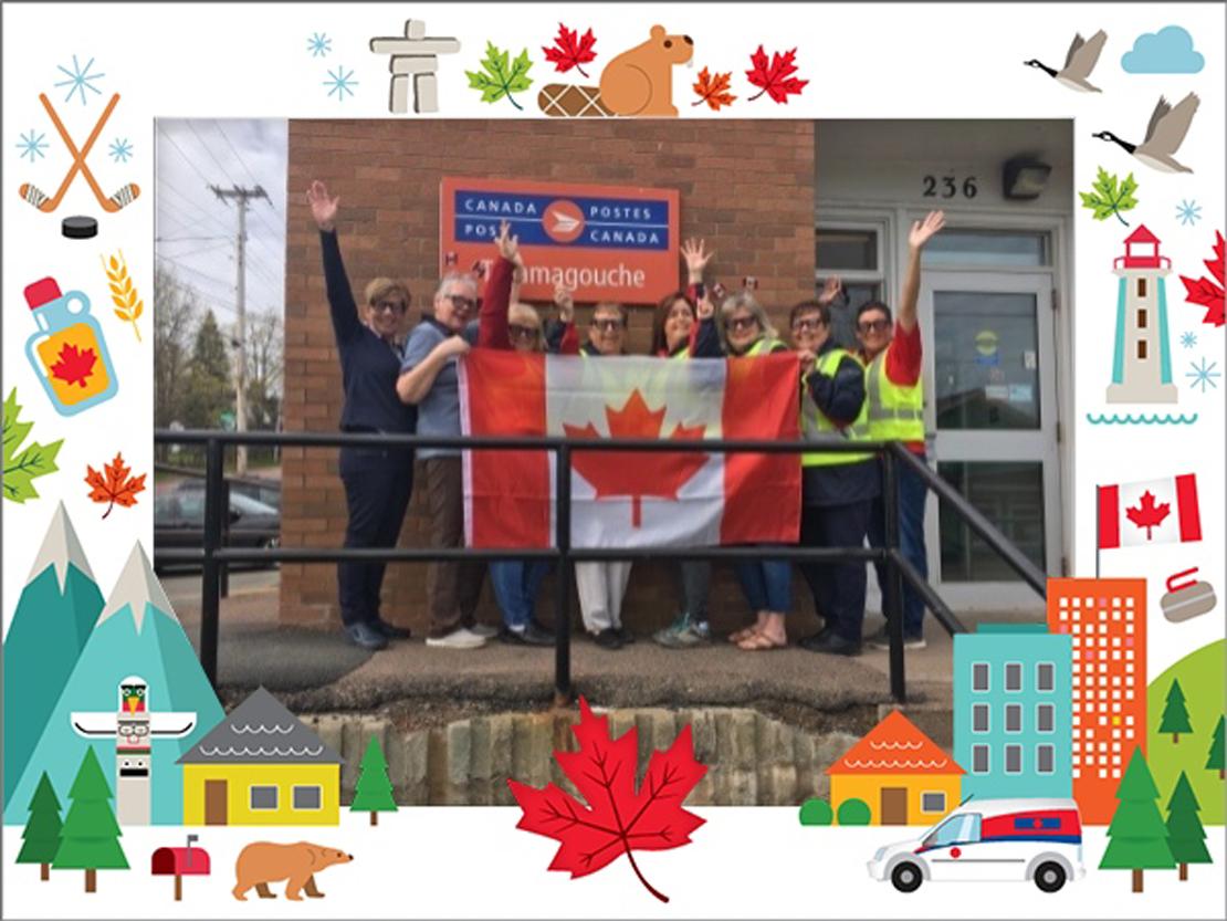 Un groupe d'employés de Postes Canada prend la pose avec le drapeau du Canada devant le bureau de poste de Tamagouche, en Nouvelle-Écosse.