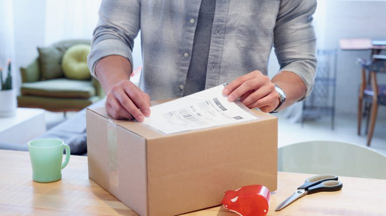A man applies a return shipping label to a box.