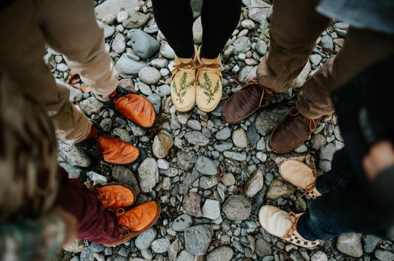 Cinq personnes se tiennent debout en cercle et portent des mocassins faits à la main de la marque Jamie Gentry Designs.