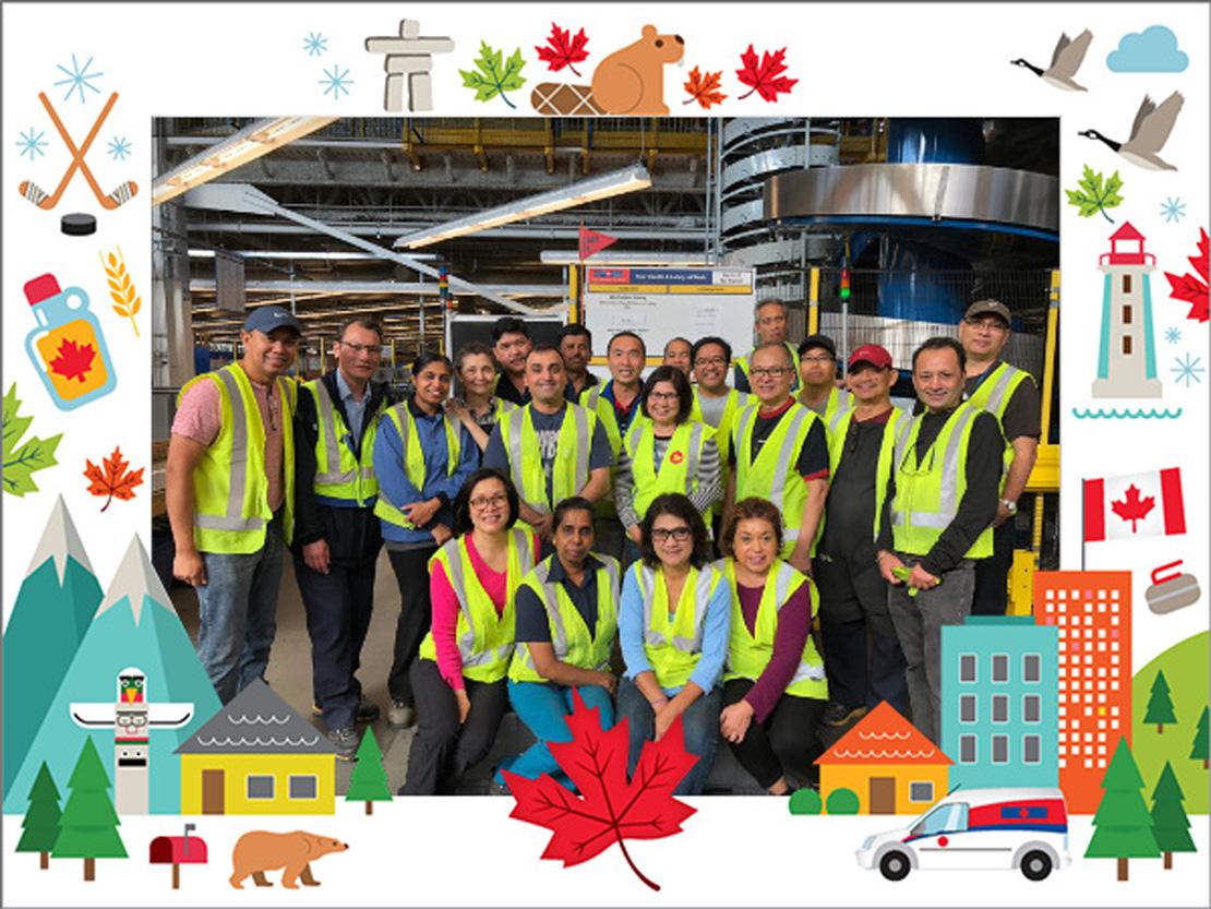 Des employés de Postes Canada prennent la pose pour une photo de groupe.