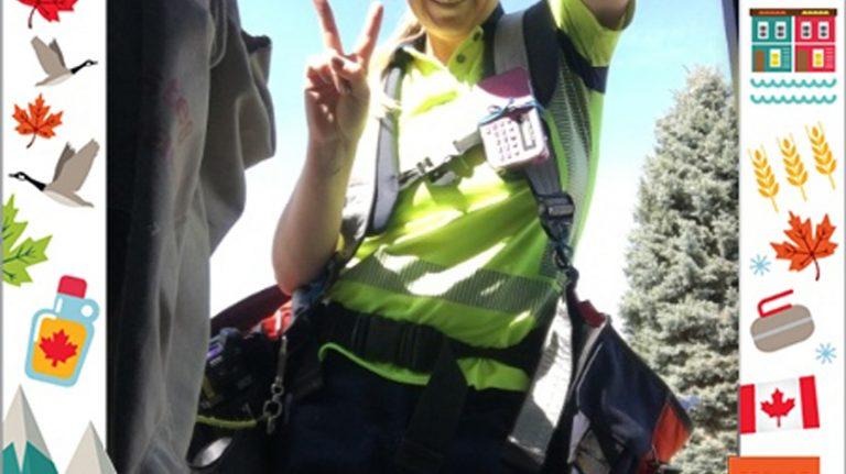 Une employée de Postes Canada, tout sourire, fait un signe de la paix avec les doigts.