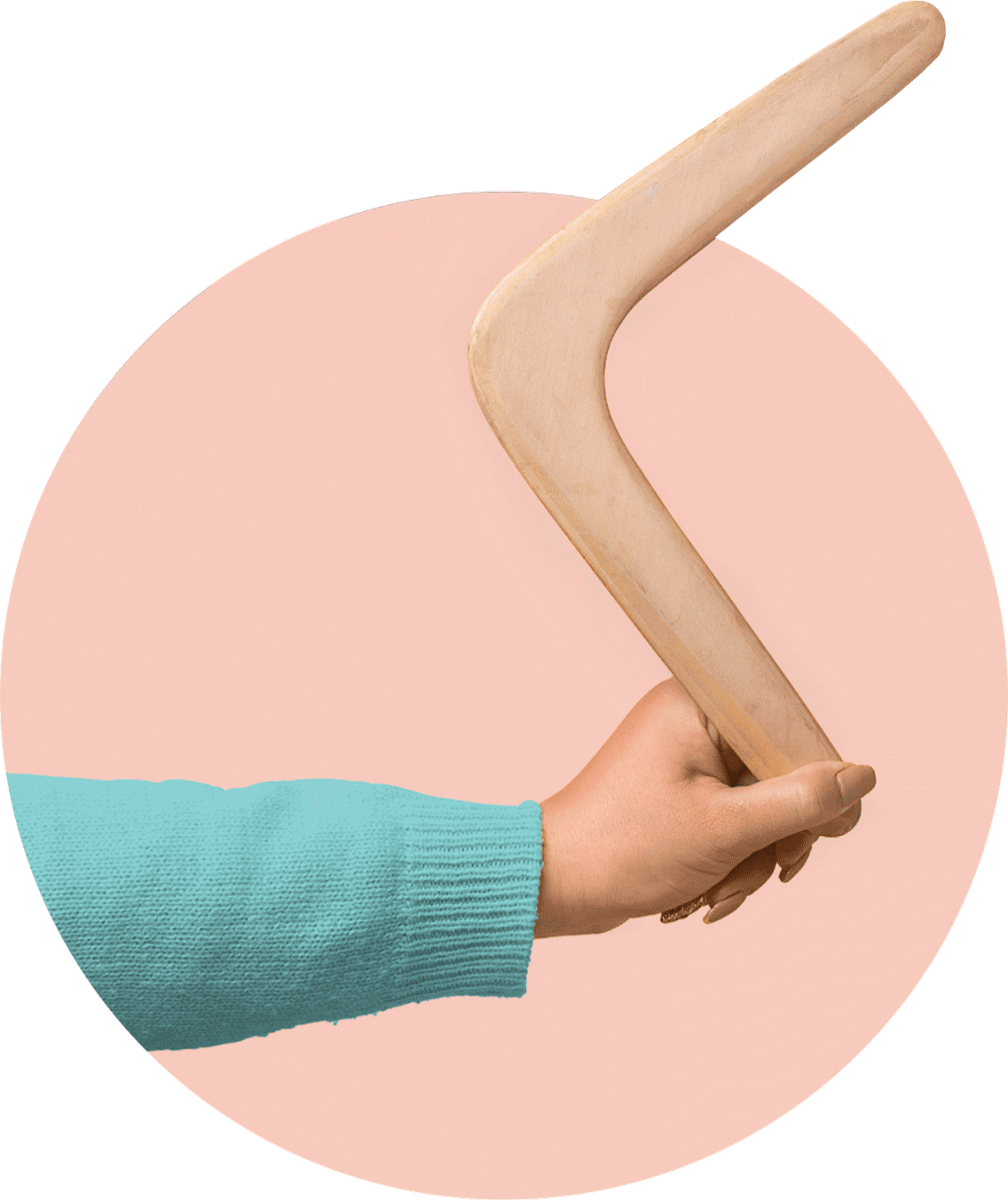 A woman in a pale green sweater holds a wooden boomerang.