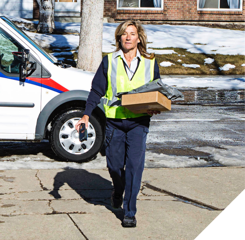 Canada Post employee walks on an icy road carrying multiple parcels.
