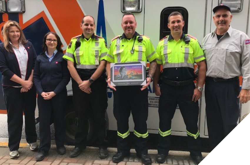 Canada Post employees present a commemorative plaque of the Emergency Responders stamp to paramedics in Timmins, Ont.